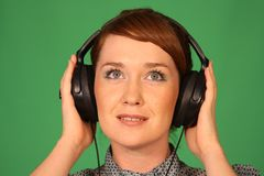 Girl in headphones. Girl with headphones on green background Stock Images
