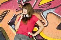 Girl with headphones and graffiti wall Royalty Free Stock Photography