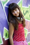 Girl with headphones and graffiti wall Royalty Free Stock Photo