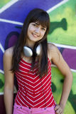 Girl with headphones and graffiti wall Stock Photos
