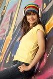 Girl with headphones and graffiti wall at bac Stock Photo