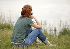 Girl with headphones at grass Stock Images