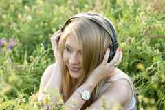 Girl with headphones on the grass. One of the photos Made during a photo shoot of Russian girl in summer at sunset Stock Images