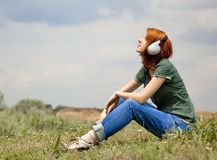 Girl with headphones at grass in spring time. Stock Images