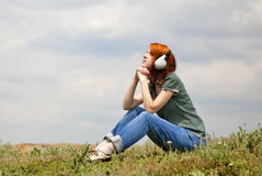 Girl with headphones at grass in spring time. Royalty Free Stock Image