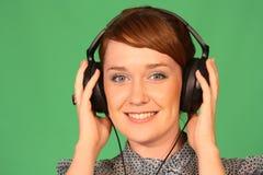 Girl in headphones. Girl with headphones on green background Stock Photos