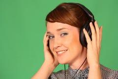 Girl in headphones. Girl with headphones on green background Stock Image
