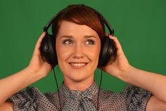 Girl in headphones. Girl with headphones on green background Royalty Free Stock Photos