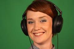 Girl in headphones. Girl with headphones on green background Stock Photo