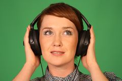 Girl in headphones. Girl with headphones on green background Royalty Free Stock Image