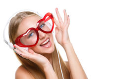 Girl in headphones and heart shaped glasses Royalty Free Stock Photo