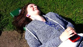 Girl with headphones in her ears laughs with joy lying on a bench stock footage