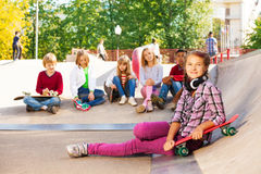 Girl with headphones holds skateboard and mates Stock Image