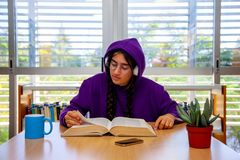 Girl with headphones and hood and urban look, consult a book in an office. Girl with headphones and hood, dressed in casual clothes and urban look, consult a stock images