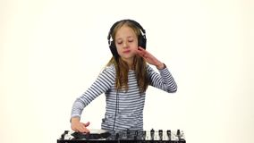 Girl in headphones jumps for turntable. White background, slow motion. Teen girl dj in headphones jumps for turntable, dancing to music, hands playing on vinyl stock video footage