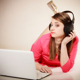 Girl with headphones and laptop listening to music Royalty Free Stock Photography