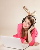 Girl with headphones and laptop listening to music Royalty Free Stock Images