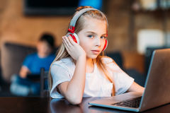 Girl in headphones with laptop on tabletop looking at camera Stock Photos