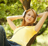 Girl with headphones lie over tree Stock Photo