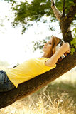 Girl with headphones lie over tree Royalty Free Stock Images