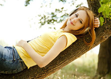 Girl with headphones lie over tree Stock Images