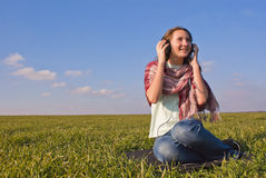 Girl with headphones listening music. Outdoors Stock Photo