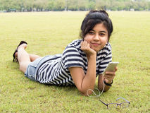 A girl with headphones. Listening music. A young girl lie down on grass with headphones outdoors. Listening music Royalty Free Stock Photos