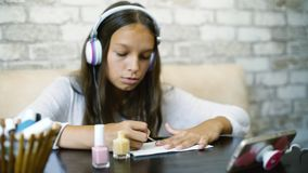 Girl in headphones listening music on phone making manicure applying nail polish free copy space. Cute teenager girl in headphones listening music on phone while stock photo
