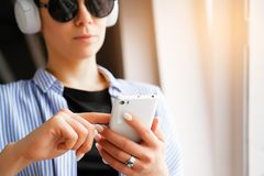 Girl with headphones listening to music, looking at the phone, while in the room, airport, office. Mobile phone in the hands of royalty free stock images