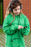 Girl in headphones listening to music on mobile phone. Outside Royalty Free Stock Photo