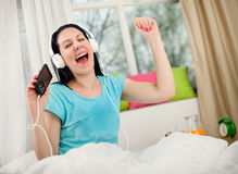 Girl in headphones listening to music from smartphone and dancin Royalty Free Stock Photo