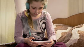 Girl with headphones listening to music from smartphone stock video footage