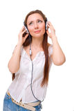 Girl in headphones listens to music looking up Royalty Free Stock Images