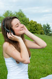 Girl in headphones listens to music in the park. Royalty Free Stock Image