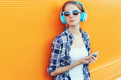 Girl in headphones listens to music using smartphone over colorful. Background Stock Images