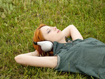 Girl with headphones lying at green grass in sprin Royalty Free Stock Images