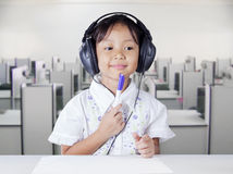 Girl with headphones in multimedia room Stock Image