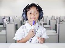 Girl with headphones in multimedia room Stock Image