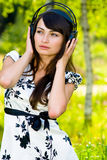 Girl in headphones on nature. The young beautiful woman listens to music through ear-phones against a birchwood Royalty Free Stock Photo