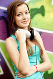 girl with headphones near graffiti background. Royalty Free Stock Photos
