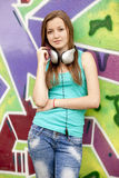 Girl with headphones near graffiti background. Royalty Free Stock Images