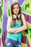 Girl with headphones near graffiti background. stock images