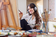 Girl in headphones  paints with oil colors on canvas Royalty Free Stock Image