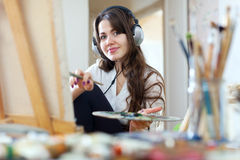 Girl in headphones  paints with oil colors Royalty Free Stock Images