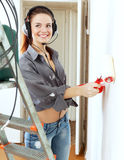 Girl in headphones paints wall Stock Photo
