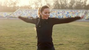 Girl in headphones performs fitness exercises in the autumn morning stock video