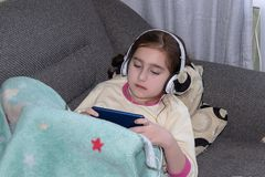 Girl with headphones playing in the phone royalty free stock photos