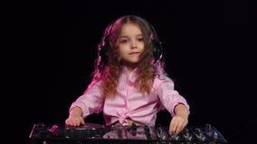 Girl in headphones plays on turntable. Black background, slow motion. Little girl in headphones plays on turntable, on head of child wearing black headphones stock video footage