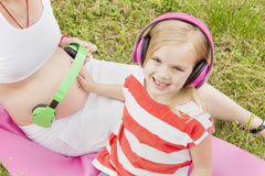 Girl with headphones and a pregnant mom royalty free stock images