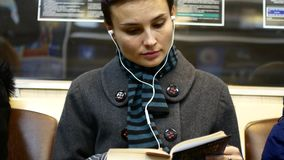 Girl in headphones reading a book in the subway.  stock footage
